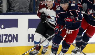 Columbus Blue Jackets forward Cam Atkinson, right, controls the puck in front of Colorado Avalanche forward Andre Burakovsky, of Austria, during the second period of an NHL hockey game in Columbus, Ohio, Saturday, Feb. 8, 2020. (AP Photo/Paul Vernon)
