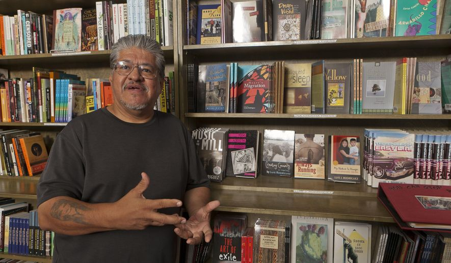 "FILE - In this file photo taken Monday, Sept. 12, 2011, writer and activist Luis J. Rodriguez poses for a photo at his independent bookstore and community center ""Tia Chucha"" in Los Angeles. Rodriguez's collection of essays released Jan. 28, 2020 is among the books Latinos are recommending via social media amid the controversy surrounding the novel, ""American Dirt."" (AP Photo/Damian Dovarganes,File)"