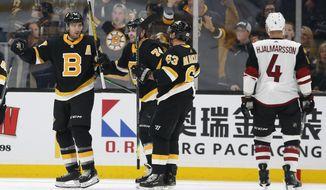 Boston Bruins' Patrice Bergeron, left, celebrates his goal with teammates Brad Marchand (63) and Jake DeBrusk as Arizona Coyotes' Niklas Hjalmarsson (4) skates away during the second period of an NHL hockey game Saturday, Feb. 8, 2020, in Boston. (AP Photo/Winslow Townson)