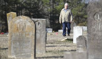In this Tuesday, Jan. 21, 2020 photo, Ralph Farrell walks through the Red Banks cemetery in Red Banks Mississippi where more than 200 markers indicate recently discovered remains of enslaved persons.(Thomas Wells//The Northeast Mississippi Daily Journal via AP)