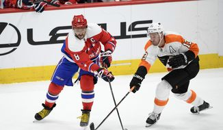 Washington Capitals left wing Alex Ovechkin (8), of Russia, works for the puck next to Philadelphia Flyers center Kevin Hayes (13) during the second period of an NHL hockey game Saturday, Feb. 8, 2020, in Washington. (AP Photo/Nick Wass) ** FILE **