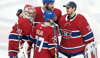 Montreal Canadiens goaltender Carey Price, left, celebrates with teammates Brett Kulak (77) Jeff Petry (26) and goalie Charlie Lindgren after defeating the Toronto Maple Leafs in an NHL hockey game in Montreal, Saturday, Feb. 8, 2020. (Graham Hughes/The Canadian Press via AP)