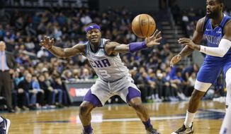 Charlotte Hornets guard Terry Rozier, left, beats Dallas Mavericks guard Tim Hardaway Jr. to a loose ball during the first half of an NBA basketball game in Charlotte, N.C., Saturday, Feb. 8, 2020. (AP Photo/Nell Redmond)