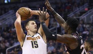 Denver Nuggets center Nikola Jokic (15) looks to shoot as Phoenix Suns center Deandre Ayton (22) defends during the first half of an NBA basketball game, Saturday, Feb. 8, 2020, in Phoenix. (AP Photo/Ralph Freso)