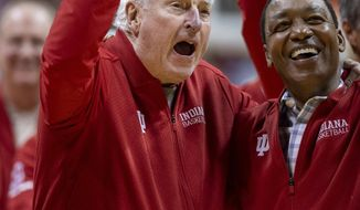 "Former Indiana basketball head coach Bobby Knight, left, yells ""play defense!"" for the fans during his first appearance at Indiana University since his dismissal in September of 2000. Knight, along with former player Isiah Thomas, right, are on the court during a ceremony with the Indiana players of the 1980 Big Ten championship team the halftime of an NCAA college basketball game, Saturday, Feb. 8, 2020, in Bloomington, Ind. (AP Photo/Doug McSchooler)"