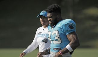 Carolina Panthers coaching intern Jennifer King, left, talks with Elijah Holyfield (33) during practice at the NFL football team's training camp in Spartanburg, S.C., Monday, July 29, 2019. (AP Photo/Chuck Burton)  **FILE**