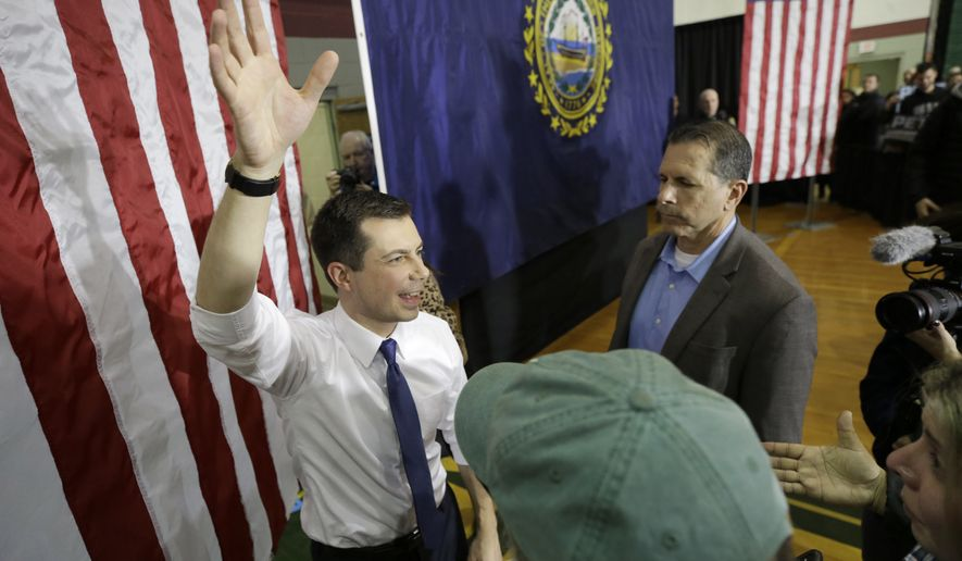 Democratic presidential candidate former South Bend, Ind., Mayor Pete Buttigieg, left, waves at the conclusion of a campaign rally, Sunday, Feb. 9, 2020, in Dover, N.H. (AP Photo/Steven Senne)