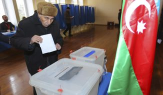 A man casts his ballot at a polling station during parliamentary elections in Baku, Azerbaijan, Sunday, Feb. 9, 2020. Snap parliamentary elections are held in Azerbaijan after President Ilham Aliyev dissolved parliament in December. Many opposition parties say they didn't have time to prepare for the campaign and have decided to boycott the elections. (AP Photo/Aziz Karimov)