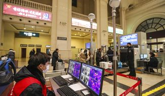 FILE - In this Jan. 21, 2020, file photo, a worker monitors display screens for infrared thermometers as they check travelers at Hankou Railway Station in Wuhan in southern China's Hubei province before authorities seals the city. For weeks after the first reports of a mysterious new virus in Wuhan, people poured out of the central Chinese city, cramming onto buses, trains and airplanes as the first wave of China's great Lunar New Year migration broke across the nation. Some carried with them a new virus that has claimed over 560 lives and sickened more than 28,000 people. (Chinatopix via AP, File)