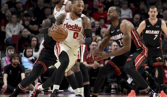 Portland Trail Blazers guard Damian Lillard, left, dribbles the ball around, Miami Heat guard Andre Iguodala, right, during the first half of an NBA basketball game in Portland, Ore., Sunday , Feb. 9, 2020. (AP Photo/Steve Dykes)