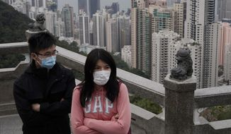 Tourists wear masks at the Peak, a popular tourist spot in Hong Kong, Sunday, Feb. 9, 2020. Health authorities are scrambling to halt the spread of a new virus that has killed hundreds in China, restricting visitors from the country and confining thousands on cruise ships for extensive screening after passengers have tested positive. (AP Photo/Kin Cheung)