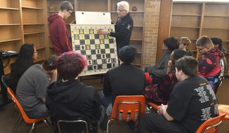 United Township student Seth Bealer and Dr. Thomas Ebalo stands with a large chess practice game board as Ebalo talks about some of the basic chess moves to United Township students during first practice at the school old library, Tuesday, Jan. 21, 2020, in East Moline, Ill. United Township high school is starting a chess club. (Gary Krambeck/Quad City Times via AP)