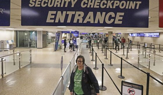 In this Jan. 31, 2020, photo, Ann Lovell stands at the security checkpoint before her flight from Salt Lake City International Airport to San Diego. Lovell travels every few months to Tijuana, Mexico, to buy medication for rheumatoid arthritis — with tickets paid for by the state of Utah's public insurer. Lovell is one of about 10 state workers participating in a year-old program to lower prescription drug costs by having public employees buy their medication in Mexico at a steep discount compared to U.S. prices. (AP Photo/Rick Bowmer)