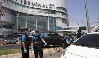 Forensic officers inspect a shooting scene outside the Terminal 21 Korat mall in Nakhon Ratchasima, Thailand, Sunday, Feb. 9, 2020. Thai officials say a soldier who went on a shooting rampage and killed numerous people and injured dozens of others has been shot dead inside the mall in northeastern Thailand. (AP Photo/Wason Wanichakorn)