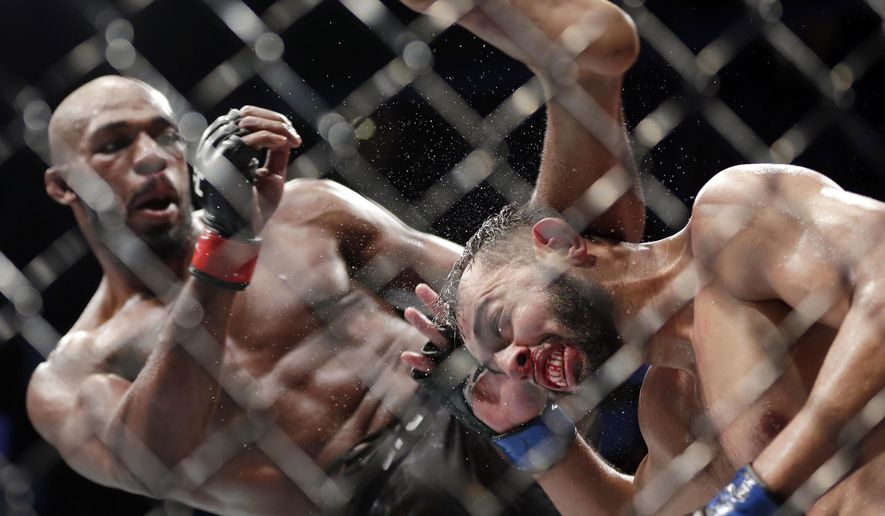 Jon Jones, left, delivers a kick to Dominick Reyes, right, during a light heavyweight mixed martial arts bout at UFC 247 Sunday, Feb. 9, 2020, in Houston. (AP Photo/Michael Wyke)