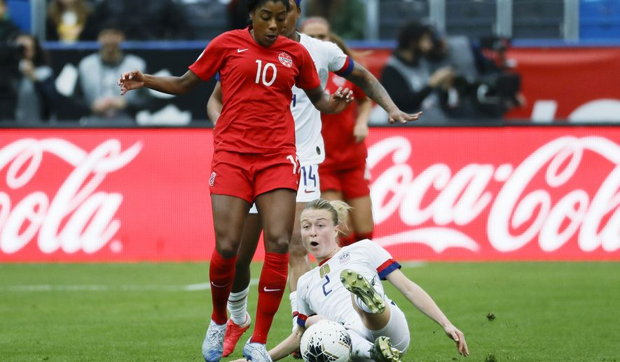 U.S. defender Emily Sonnett, right, kicks the ball away from Canada defender Ashley Lawrence during the first half of a CONCACAF women's Olympic qualifying soccer match Sunday, Feb. 9, 2020, in Carson, Calif. (AP Photo/Chris Carlson)