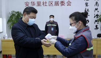In this photo released by Xinhua News Agency, Chinese President Xi Jinping, left, wearing a protective face mask receives a temperature check as he inspects the novel coronavirus pneumonia prevention and control work at a neighbourhoods in Beijing, Monday, Feb. 10, 2020. China reported a rise in new virus cases on Monday, possibly denting optimism that its disease control measures like isolating major cities might be working, while Japan reported dozens of new cases aboard a quarantined cruise ship. (Pang Xinglei/Xinhua via AP)