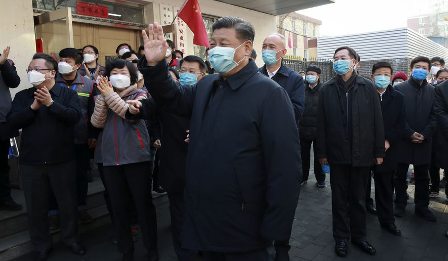 In this photo released by Xinhua News Agency, Chinese President Xi Jinping, centre, wearing a protective face mask waves as he inspects the novel coronavirus pneumonia prevention and control work at a neighbourhoods in Beijing, Monday, Feb. 10, 2020. China reported a rise in new virus cases on Monday, possibly denting optimism that its disease control measures like isolating major cities might be working, while Japan reported dozens of new cases aboard a quarantined cruise ship. (Pang Xinglei/Xinhua via AP)