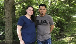 In this June 21, 2019, file photo, Alyse Sanchez and her husband, Elmer Sanchez, pose for The Associated Press in Sandy Spring, Md. A federal judge in Maryland has banned immigration officials from arresting, detaining and deporting immigrants who are seeking legal status based on their marriages to U.S. citizens. (AP Photo/Regina Garcia Cano, File)
