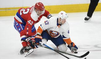 Washington Capitals defenseman Martin Fehervary (42) and New York Islanders right wing Leo Komarov (47) battle for the puck during the second period of an NHL hockey game, Monday, Feb. 10, 2020, in Washington. (AP Photo/Nick Wass)