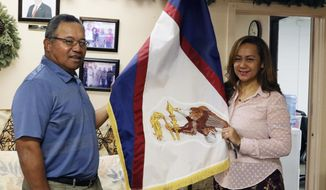 """In this Jan. 10, 2020 photo, Filipo Ilaoa, left, and Bonnelley Pa'uulu pose with the flag of American Samoa at the American Samoa government office in Honolulu. Some American Samoans worry a federal judge's recent ruling in Utah saying those born in the U.S. territory should be recognized as U.S. citizens could threaten """"fa'a Samoa,"""" or the Samoan way of life. (AP Photo/Jennifer Sinco Kelleher)"""