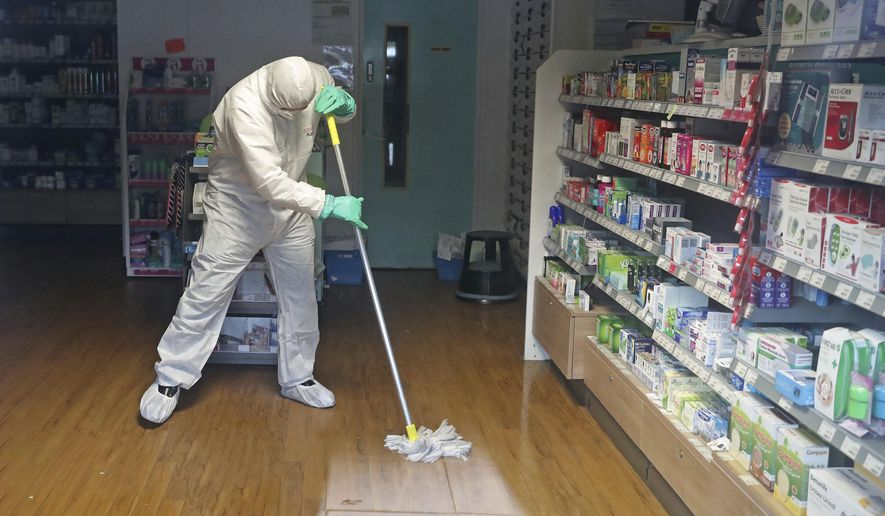 """A man in protective clothing cleans the County Oak Medical Centre GP practice which has been temporarily closed """"because of an urgent operational health and safety reason"""", following reports a member of staff there was one of those infected with coronavirus, in Brighton, England, Monday, Feb. 10, 2020.  Britain has declared the new coronavirus that emerged from China a """"serious and imminent threat to public health'' and announced new measures Monday to combat the spread of the disease. (Steve Parsons/PA via AP)"""