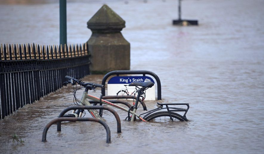 A cycle rack engulfed by floodwater after the River Ouse burst its banks in the aftermath of Storm Ciara, in York, England, Monday, Feb. 10, 2020.  Storm Ciara battered the U.K. and northern Europe with hurricane-force winds and heavy rains Sunday, halting flights and trains and producing heaving seas that closed down ports. Soccer games, farmers' markets and cultural events were canceled as authorities urged millions of people to stay indoors, away from falling tree branches.(Danny Lawson/PA via AP)