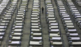 FILE - In this Feb. 4, 2020, file photo, a worker walks among beds in a convention center that has been converted into a temporary hospital in Wuhan in central China's Hubei Province. The virus outbreak that began in China and has spread to more than 20 countries is stretching already-strained public health systems in Asia and beyond, raising questions over whether everyone can get equal access to treatment. (Chinatopix via AP, File)