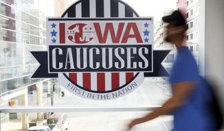 In this Feb. 4, 2020 photo, a pedestrian walks past a sign for the Iowa Caucuses on a downtown skywalk, Tuesday, Feb. 4, 2020, in Des Moines, Iowa. (AP Photo/Charlie Neibergall)