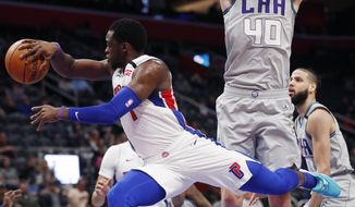 Detroit Pistons guard Reggie Jackson (1) passes around the defense of Charlotte Hornets center Cody Zeller (40) during the first half of an NBA basketball game, Monday, Feb. 10, 2020, in Detroit. (AP Photo/Carlos Osorio)
