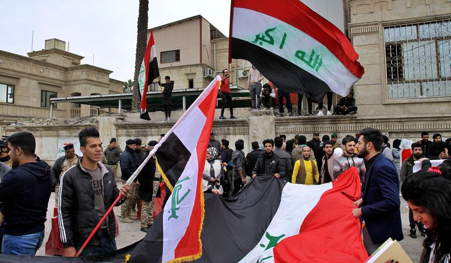 University students hold national flags during a protest in front of the Ministry of Higher Education and Scientific Research in Baghdad, Iraq, Sunday, Feb. 9, 2020. (AP Photo/Khalid Mohammed)