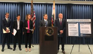 California Attorney General Xavier Becerra, second from right, announces an independent review of the Los Angeles Police Department's use of a gang member database after allegations of misuse on Monday,  Feb. 10, 2020 in Los Angeles. The California Department of Justice will review the Los Angeles Police Department's records and policies regarding use of the state's gang member database after allegations emerged that officers in an elite crime suppression team falsified records and listed innocent people as gang members, Becerra said Monday. (AP Photo/Stefanie Dazio)
