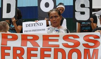 FILE - In this May 3, 2019, file photo, protesters rally outside the armed forces headquarters to mark World Press Freedom Day which was declared by the UN General Assembly in Manila, Philippines. The Philippine government's chief lawyer is asking the Supreme Court to shut down the country's largest TV network by revoking its operating franchises because of alleged constitutional violations, in a move critics call an attempt to muzzle the media. (AP Photo/Bullit Marquez, File )