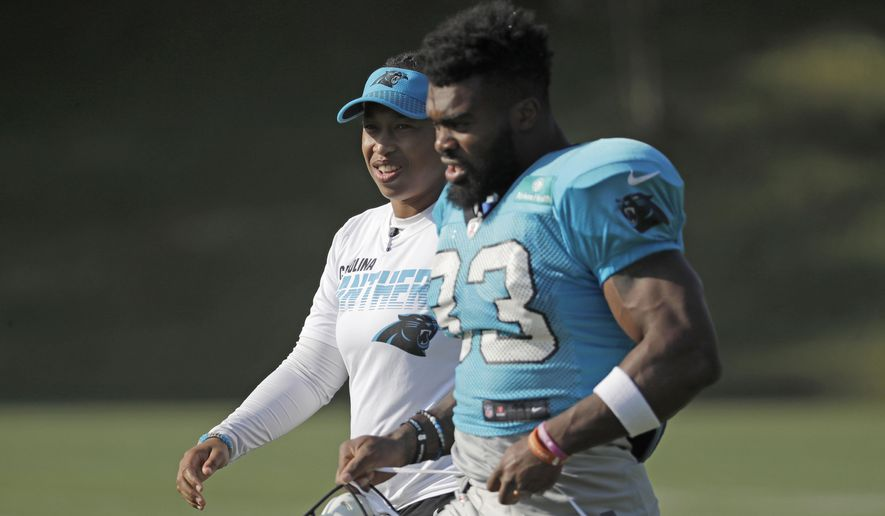FILE - In this July 29, 2019, file photo, Carolina Panthers coaching intern Jennifer King, left, talks with Elijah Holyfield (33) during practice at the NFL football team's training camp in Spartanburg, S.C. The Washington Redskins have hired Jennifer King as a coaching intern who will work with the offensive staff throughout the season. King most recently worked as an offensive assistant at Dartmouth College. Before that she interned for the Carolina Panthers. (AP Photo/Chuck Burton, File)