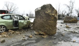 A damaged car sits next to a fallen rock in Morgantown, W.Va. Monday, Feb. 10, 2020.  Three people were taken to a hospital after the rock slide struck the car and a transit shuttle vehicle at West Virginia University. The university said the slide occurred along U.S. Route 19 after rains fell in the area. (Ron Rittenhouse/The Dominion Post via AP)