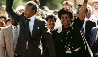 FILE - In this Feb. 11, 1990 file photo, Nelson Mandela and his wife, Winnie Madikizela-Mandela, gesture as Mandela walks free from the Victor Verster Prison in Paarl, Cape Town, South Africa after serving 27 years in prison. Tuesday, Feb. 11, 2020 marks the 30 year anniversary of the release of the former South African president. (AP Photo/Greg English, File)