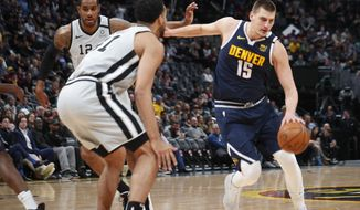 Denver Nuggets center Nikola Jokic, right, drives past San Antonio Spurs forward LaMarcus Aldridge, back left, as center Trey Lyles, front left, waits in the paint to defend in the first half of an NBA basketball game Monday, Feb. 10, 2020, in Denver. (AP Photo/David Zalubowski)