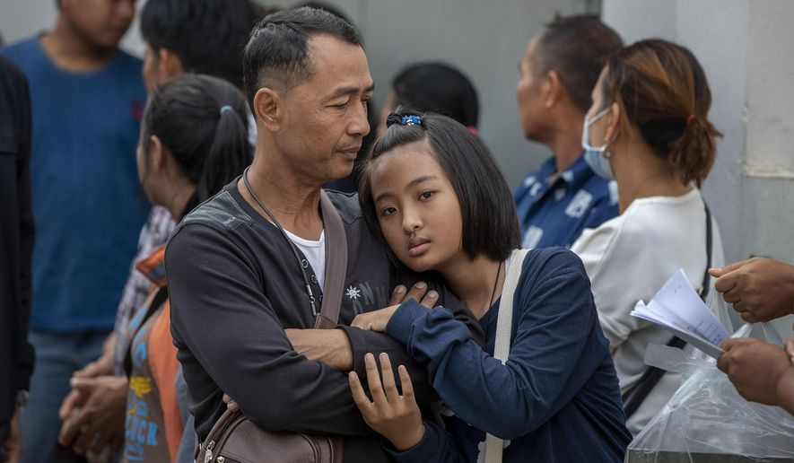 Relatives of mass shooting victims wait outside a morgue to receive the remains at a morgue in Korat, Nakhon Ratchasima, Thailand, Monday, Feb. 10, 2020. Thai officials said the attack was carried out by a single gunman, a disgruntled soldier who opened fire on strangers before he was fatally shot Sunday at a shopping mall. (AP Photo/Gemunu Amarasinghe)