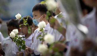 Assumption kindergarten's children offer flowers at the scene of a deadly mass shooting outside the Terminal 21 shopping mall in Korat, Nakhon Ratchasima, Thailand Tuesday, Feb. 11, 2020. A soldier carried out the country's worst mass shooting in an hourslong siege at the shopping mall. (AP Photo/Sakchai Lalit)