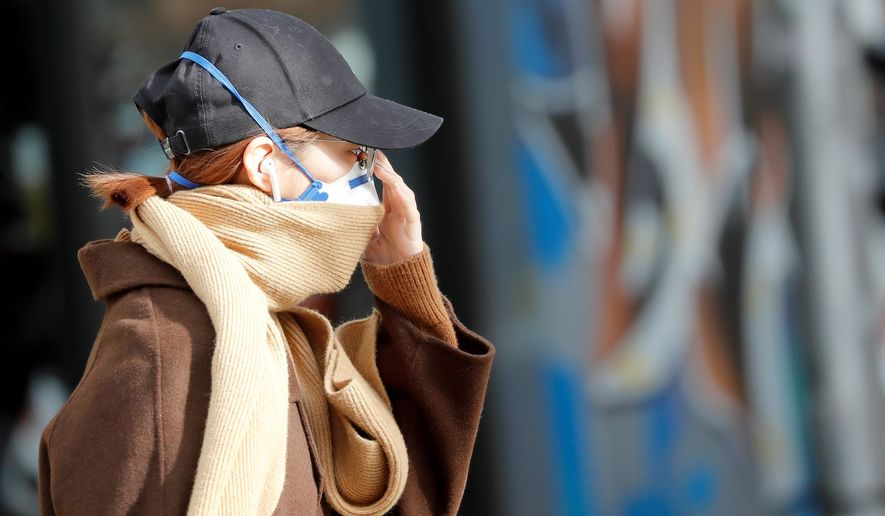 A woman in Britain walks the street in surgical mask as concerns over the COVID-19 grow on a global scale. (Associated Press)