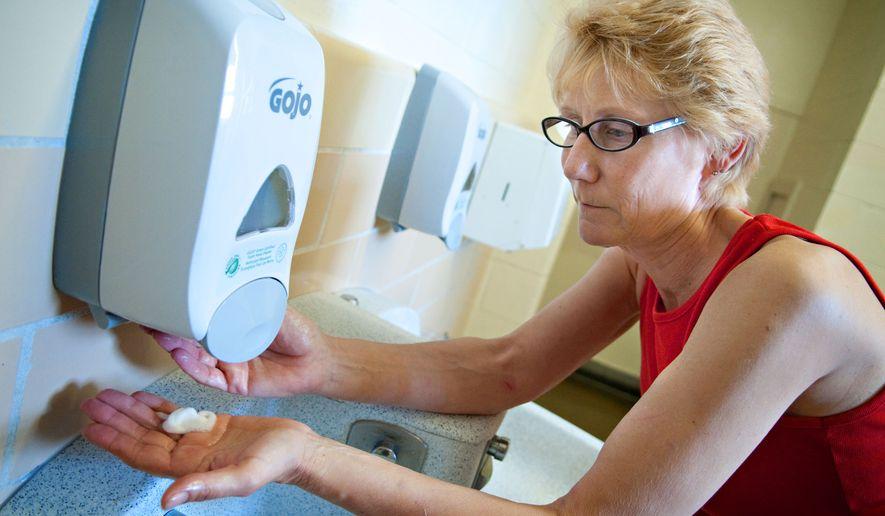 Custodial Engineer Elizabeth Rathbun checks one of the new soap dispensers at Washburn High School in Minneapolis, Friday, Aug. 14, 2009. (AP Photo/Dawn Villella) **FILE**