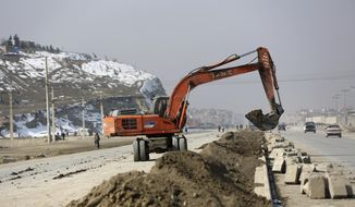 In this Monday, Feb. 10, 2020 photo, an excavator works on road construction project funded by the government, in Kabul, Afghanistan. Rebuilding war-ravaged Afghanistan has cost thousands of lives according to a new report released Monday by a U.S. government watchdog that monitors the billions of U.S. dollars spent reconstructing Afghanistan. (AP Photo/Rahmat Gul)