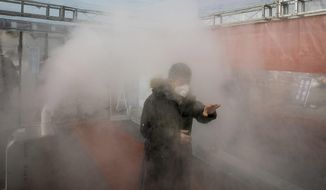 A man walks through a disinfectant spray in order to return home at a residential complex in northern China's Tianjin Municipality Tuesday, Feb. 11, 2020. China's daily death toll from a new virus topped 100 for the first time and pushed the total past 1,000 dead, authorities said Tuesday after leader Xi Jinping visited a health center to rally public morale amid little sign the contagion is abating. (Chinatopix Via AP) CHINA OUT