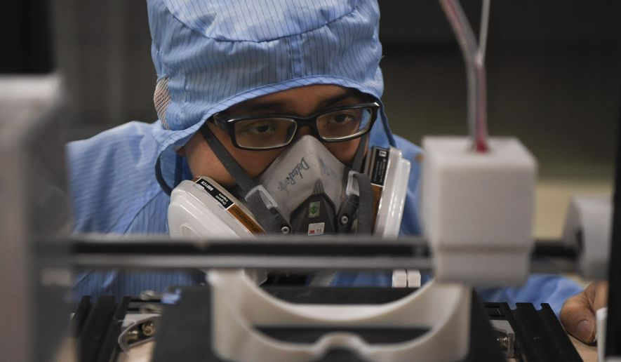 In this photo released by Xinhua News Agency, a worker inspects the operation of a 3D printer at the additive manufacturing research and application center of the Hunan Vanguard Group Co., Ltd. in the economic development zone of Changsha city in central China's Hunan Province, on Tuesday, Feb. 11, 2020. The company has been producing goggles for medical use with more than 50 3D printers working day and night for use in hospital fighting the novel coronavirus outbreak. (Xue Yuge/Xinhua via AP)