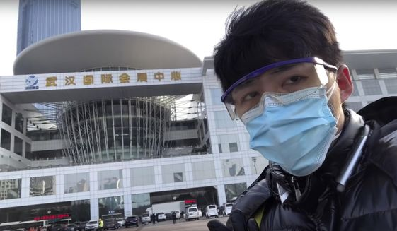 In this image from video taken Feb. 4, 2020 and released by Chen Qiushi, Chinese citizen journalist Chen Qiushi speaks in front of a convention center-turned makeshift hospital amid a viral epidemic in Wuhan in central China's Hubei province.  Armed with smart phones and social media accounts, Chen and other citizen journalists in China are telling stories from the deadly epidemic in their own words, defying the ruling Communist Party's monopoly on information. Chen disappeared last week after garnering millions of views online. (Courtesy of Chen Qiushi via AP)