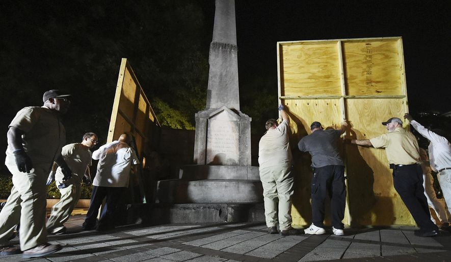 In an Aug. 15, 2017, file photo, Birmingham city workers use plywood panels to cover the Confederate Monument in Linn Park, in Birmingham, Ala., on orders from Mayor William Bell. Birmingham Mayor Randall Woodfin on Tuesday, Feb. 11, 2020, criticized an Alabama law forbidding the majority-black city from removing, or altering, a Confederate monument as well as new proposal to fine cities $10,000-a-day for violations. Birmingham faces a $25,000 fine for putting wooden panels around a Confederate monument in Linn Park.(Joe Songer/The Birmingham News via AP, File)