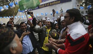 """Supporters of the Aam Aadmi Party, or """"common man's"""" party, celebrate as initial results show the party in the lead, at their party office in New Delhi, India, Tuesday, Feb. 11, 2020.  The polls put Indian Prime Minister Narendra Modi's Bharatiya Janata Party against the incumbent Aam Aadmi Party, whose pro-poor policies have focused on fixing state-run schools and providing free health care and bus fares for women during the five years in power. (AP Photo/Altaf Qadri)"""