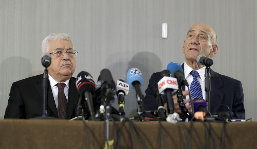 Palestinian President Mahmoud Abbas, left, listens while former Israeli Prime Minister Ehud Olmert speaks during a news conference in New York, Tuesday, Feb. 11, 2020. (AP Photo/Seth Wenig)