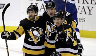 Pittsburgh Penguins' Evgeni Malkin (71) celebrates his goal with Bryan Rust (17) and Patric Hornqvist (72) during the first period of an NHL hockey game against the Tampa Bay Lightning in Pittsburgh, Tuesday, Feb. 11, 2020. (AP Photo/Gene J. Puskar)