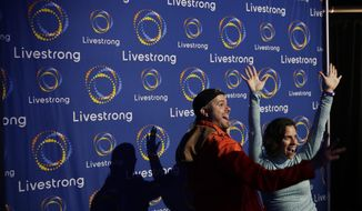 In this Monday, Feb. 3, 2020 photo, guest pose with a new logo for Livestrong at an event in Austin, Texas. The Livestrong cancer charity is on a mission to reinvent itself. It has survived a dramatic fall in contributions and donations since founder Lance Armstrong's performance-enhancing drug scandal. (AP Photo/Eric Gay)